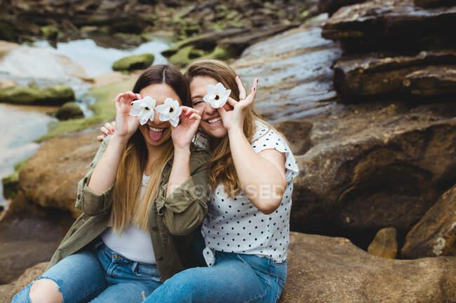 Jeunes voyageuses assises sur la pierre et couvrant les yeux de fleurs — Photo de stock