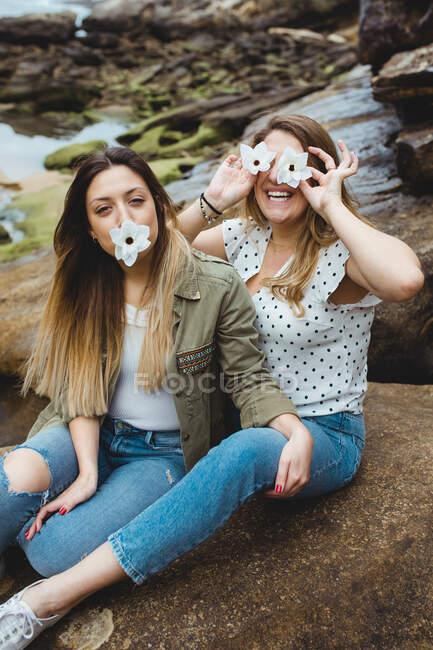 Jeunes voyageurs féminins assis sur la pierre et couvrant les yeux avec f — Photo de stock