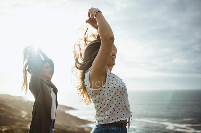 Felices viajeros femeninos disfrutando de la libertad en la playa - foto de stock
