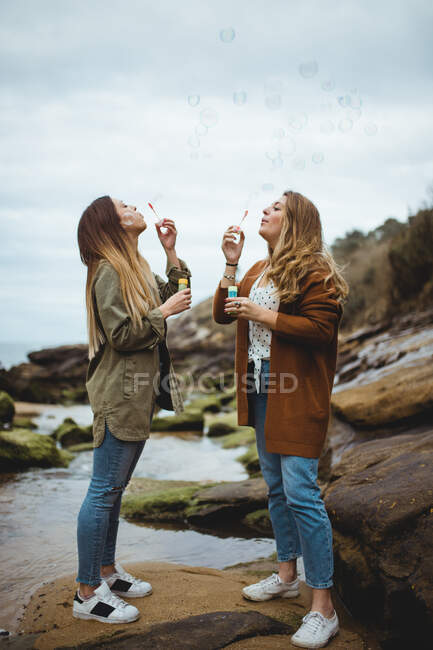 Счастливые подруги пускают пузыри на берег моря — стоковое фото