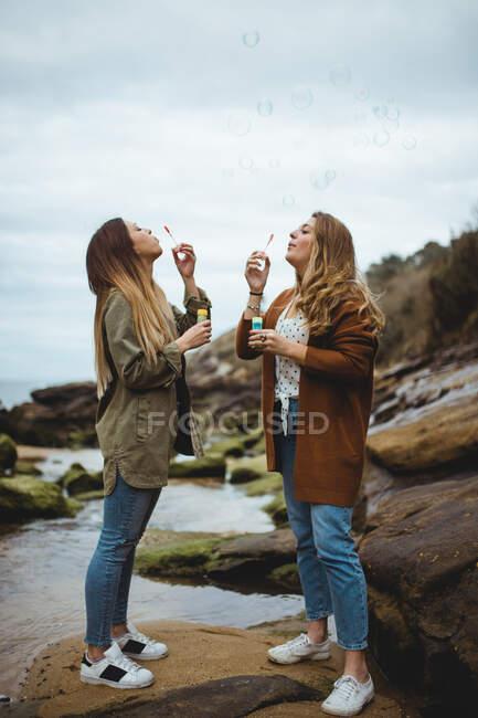 Happy female friends blowing bubbles on seashore — Stock Photo
