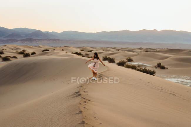Vue arrière de la jeune femme marchant dans le désert laissant des empreintes de pas dans — Photo de stock