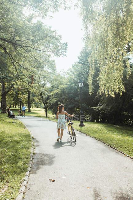 Señora casual bicicleta de ruedas en el hermoso parque - foto de stock