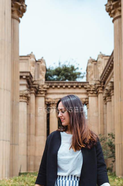 Активная женщина, идущая между древними колоннами здания снаружи — стоковое фото