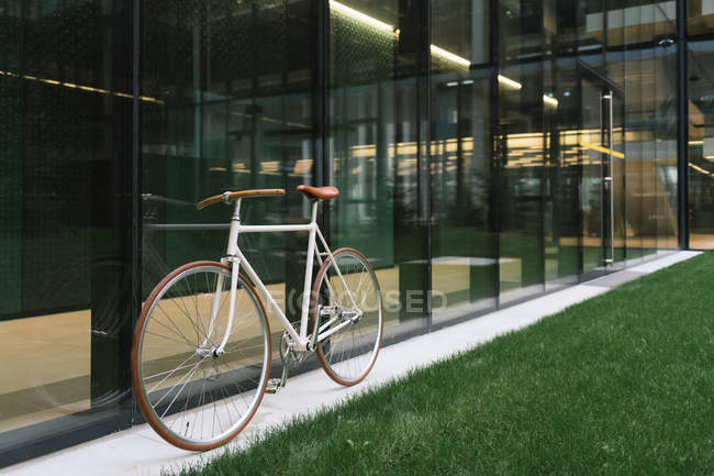 Bike parked on sidewalk near wall of contemporary building on sunny day on city street — стокове фото