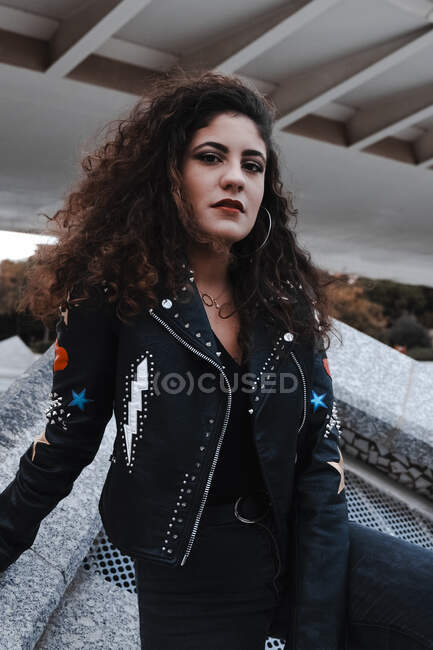 Modern woman in black jacket and jeans standing in city — Stock Photo