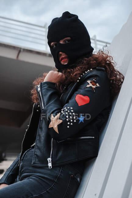 Mulher em balaclava e jaqueta de couro preto — Fotografia de Stock