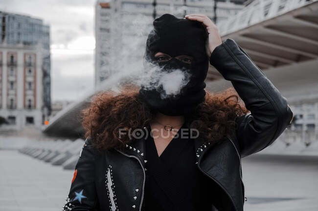 Женщина в черной маске и куртке, курящая на улице — стоковое фото