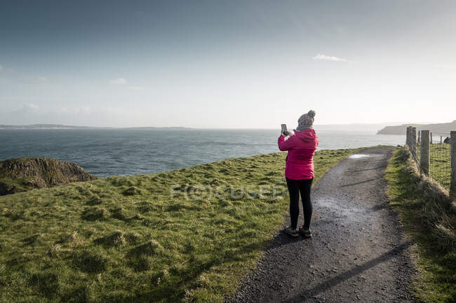 Woman standing on country road and taking picture of sea with smartphone — Stock Photo