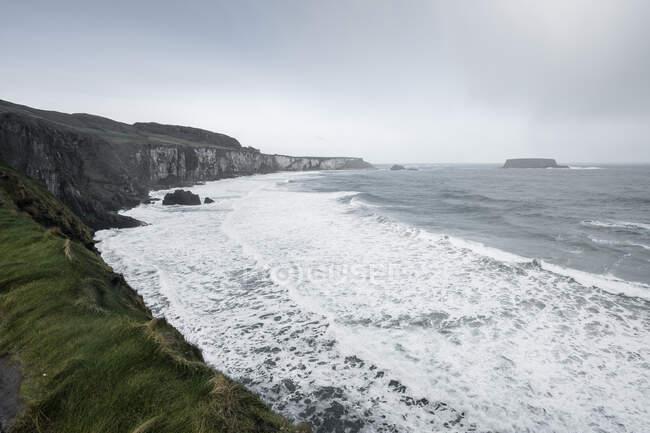 Mare mozzafiato della costa dell'Irlanda del Nord con rocce e erba verde primaverile e tempestose onde fredde che si infrangono sulla riva con schiuma — Foto stock