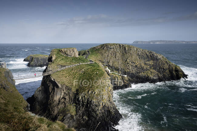 Tourist walking on rope bridge suspended between cliffs in North — Stock Photo