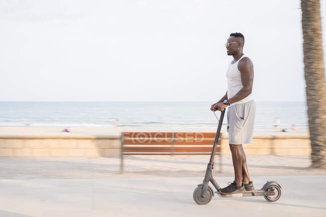Cool adult black man riding scooter in street — Stock Photo