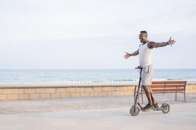 Fresco adulto nero uomo equitazione scooter in strada — Foto stock