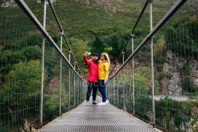 Щаслива пара подорожніх у яскравих жакетах, яка під час літніх канікул чіпляється за мобільні телефони, стоячи на підвішеному пішохідному мосту. — стокове фото