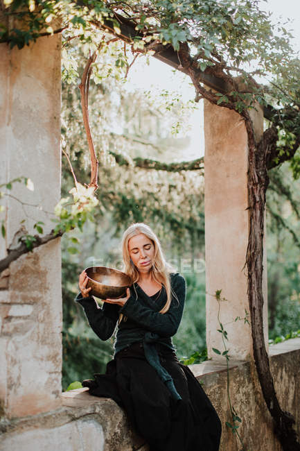 Woman in long gown clothes with closed eyes and holding metal musical bowl while sitting in ruins of old castle in historic place — Stock Photo
