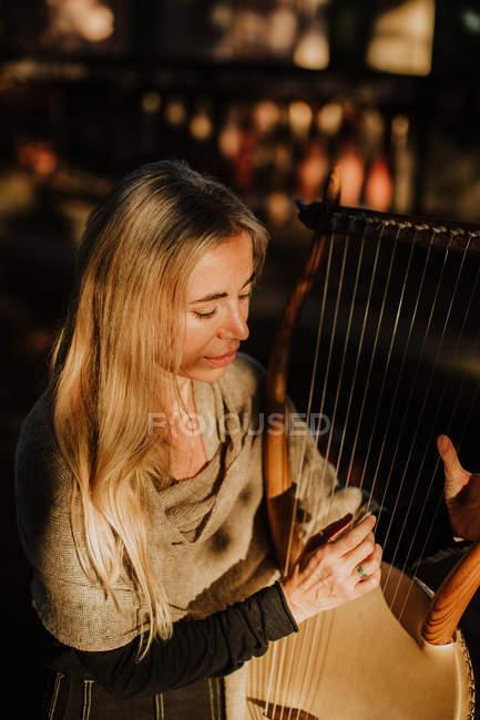 Romantische, charmante Frau mit blonden Haaren, die Melodie genießt, während sie Musikinstrument spielt und im Sommer im Garten sitzt — Stockfoto