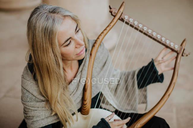 Von oben inspirierte charmante Frau mit blonden Haaren, die Musik genießt, während sie auf der Terrasse ein Streichinstrument spielt — Stockfoto