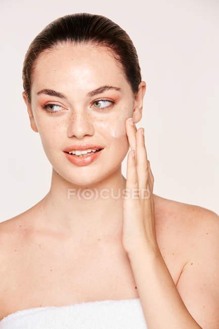Amabile donna prendersi cura del viso — Foto stock