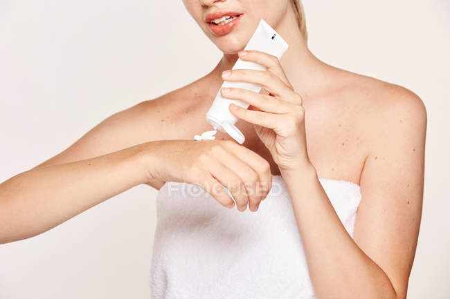 Appealing woman applying moisturizing cream on hands — стокове фото