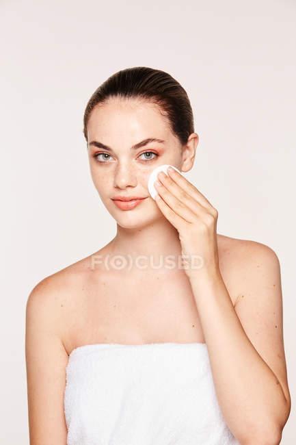 Mulher pacífica aplicando toner no rosto radiante com esponja — Fotografia de Stock