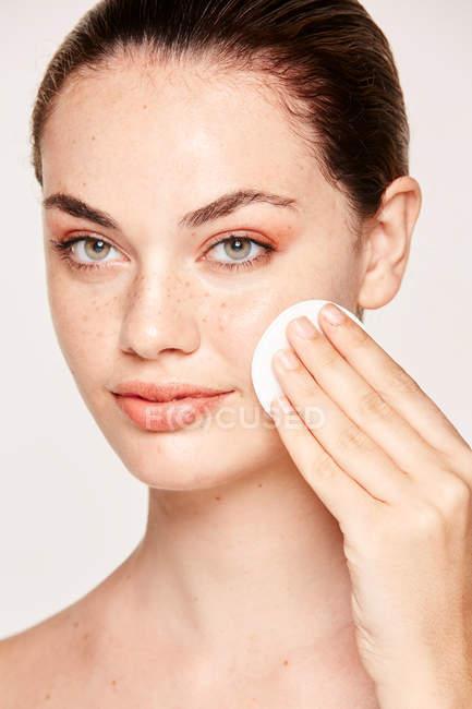 Веснушки женщина очищает лицо кожи лица с лосьоном на хлопчатобумажной губке изолированы на белом фоне — стоковое фото