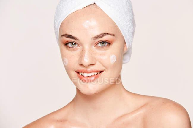Mulher sardenta positiva com toalha na cabeça e pele saudável cuidando do rosto com creme e olhando para a câmera isolada no fundo branco — Fotografia de Stock