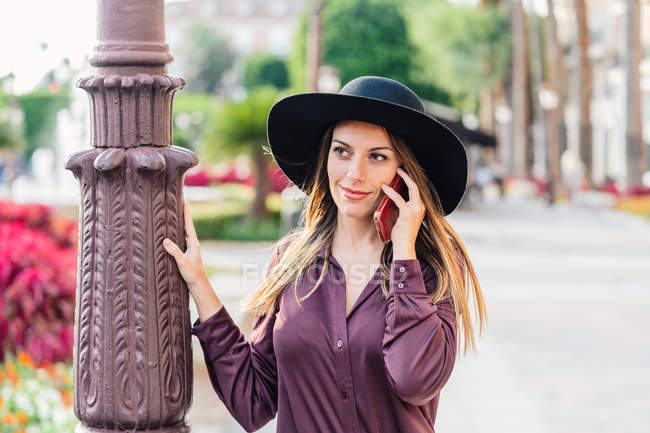 Content long haired woman in fashionable black hat and shirt walking on the street while calling on mobile phone and looking away — Stock Photo