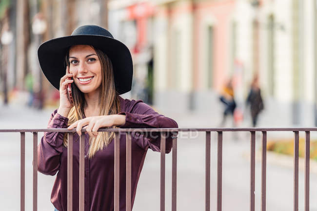 Content long haired woman in fashionable black hat and shirt leaning on fence while calling on mobile phone and looking at camera — Stock Photo