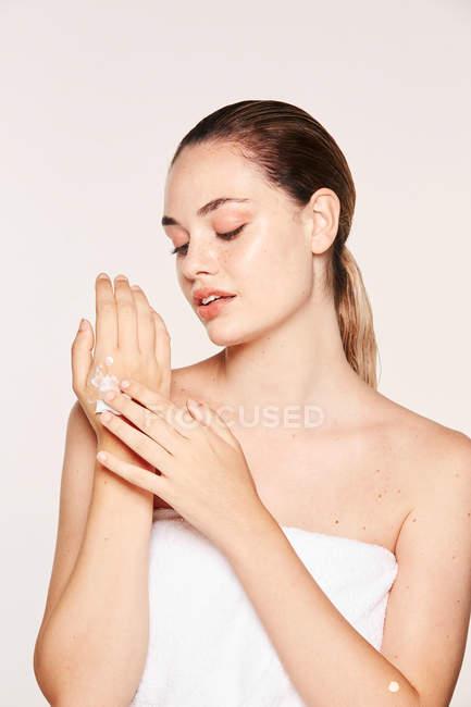 Donna deliziata che applica la crema di recupero sulle mani — Foto stock