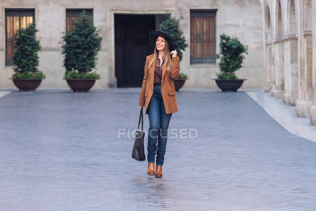 Excited woman in stylish casual wear and black hat walking and looking away on sidewalk among old buildings — Stock Photo