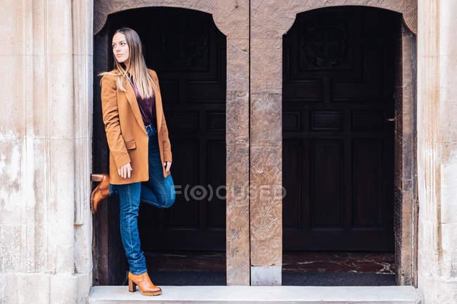 Mujer encantadora satisfecha con ropa casual elegante y tacones apoyados en la pared del edificio con arco y mirando hacia la calle de la ciudad - foto de stock
