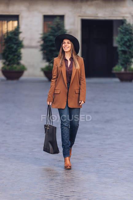 Mujer emocionada en ropa casual con estilo y sombrero negro caminando y mirando hacia la acera entre los edificios antiguos - foto de stock