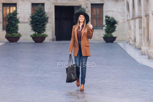 Mujer emocionada en ropa casual elegante y sombrero negro caminando y mirando a la cámara en la acera entre los edificios antiguos - foto de stock