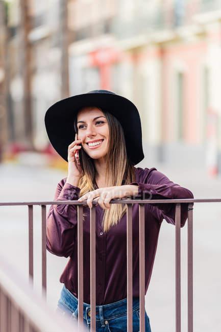 Contenuto donna dai capelli lunghi in cappello nero alla moda e camicia appoggiata alla recinzione mentre chiama il cellulare e distoglie lo sguardo — Foto stock