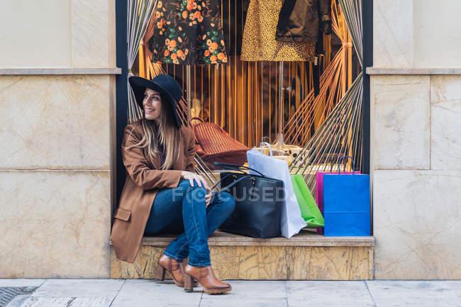 Elegante donna dai capelli lunghi che indossa un cappello shopaholic in casual abbigliamento alla moda seduto con borse della spesa su recinzione a dondolo — Foto stock
