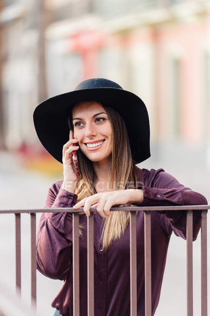 Content long haired woman in fashionable black hat and shirt leaning on fence while calling on mobile phone and looking away — Stock Photo