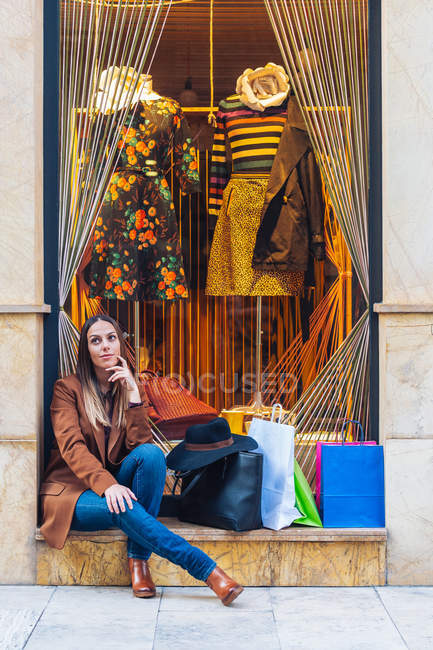Stylish long haired woman shopaholic in casual fashionable wear sitting with shopping bags on rocked fence of shop window — Stock Photo