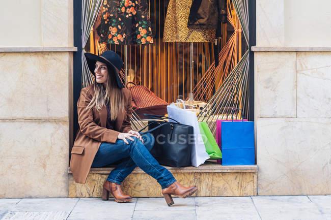 Elegante donna dai capelli lunghi che indossa un cappello shopaholic in casual alla moda indossare seduta con borse della spesa — Foto stock
