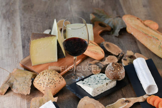 From above tasty homemade slices of white cheese and fresh crusty bread with bottle and glass of red wine on rustic wooden table — Stock Photo