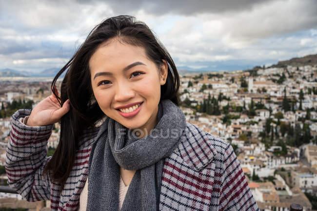 Mulher asiática feliz em casaco elegante e cachecol sorrindo e olhando para a câmera enquanto está em segundo plano borrado da cidade envelhecida — Fotografia de Stock