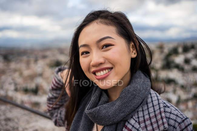 Щаслива азійка в стильному пальто і шарф посміхається і дивиться на камеру, стоячи на розмитому фоні старого міста — стокове фото