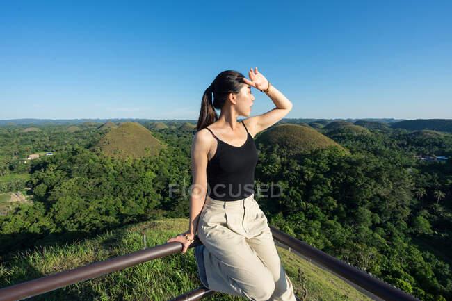 Счастливая женщина стоит на смотровой площадке на холме — стоковое фото
