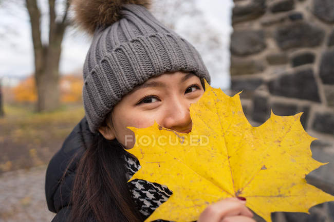 Asian woman in warm clothes looking at camera and covering face with yellow maple leaf while standing at Oslo Cathedral in Norway — Stock Photo