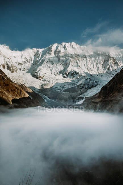 Толстый туман и облака около снежного Гималайского хребта против голубого неба в Тибете, Китай — стоковое фото