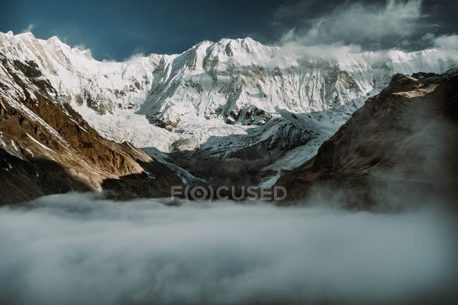 Thick mist and clouds near snowy Himalaya mountain ridge against blue sky in Tibet, China — Stock Photo