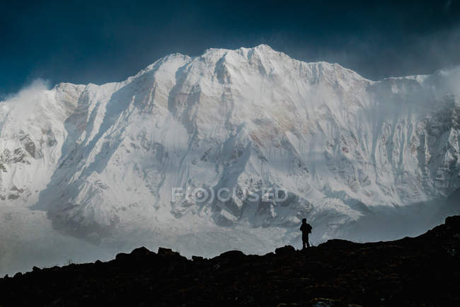 Silhouette of hiker standing on stony ground against snowy Himalaya mountain range on sunny day in Tibet, China — Stock Photo