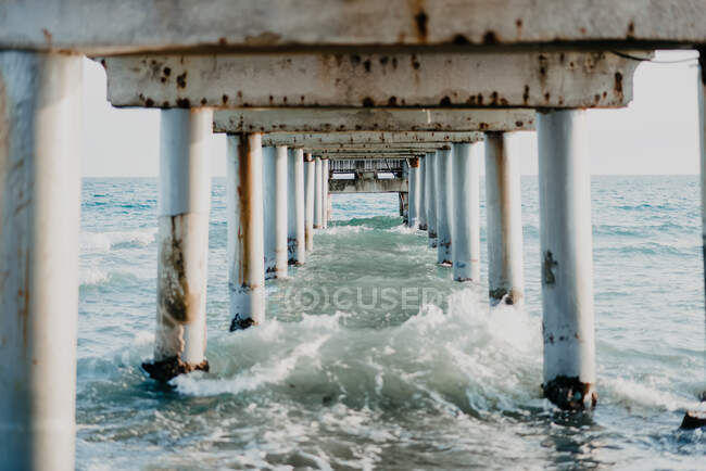 Amazing view of sea waves breaking at rusty strong pier footings into white foam on shoal under gray sky in overcast weather — Photo de stock