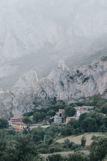 Houses of small settlement located near rough rocks of Himalaya mountain ridge on foggy day in Tibet, China — Stock Photo