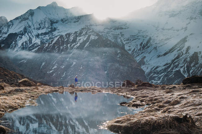 Traveler standing near calm pond against snowy Himalaya mountain ridge in cloudy morning in Tibet, China — Stock Photo