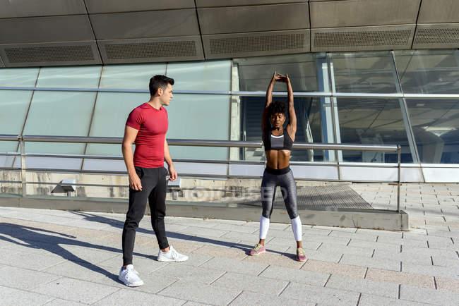 Атлетичный мужчина оказывает поддержку активной афроамериканке в выполнении упражнений на растяжку во время тренировки — стоковое фото